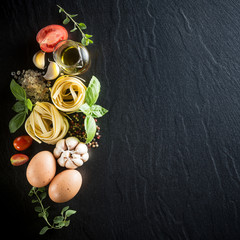 Italian food and ingredients background with fresh vegetables, eggs, tomatos, olive oil, oregano, garlic, salt, pepper, basil, pasta and spices. Top view, view from above. Copy space. Dark background.