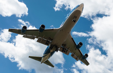 The plane on a background of blue sky and white clouds.