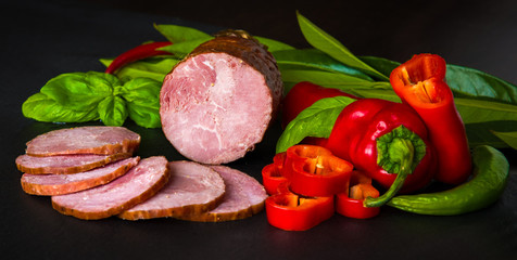 Smoked sausage, ham with red and green peppers and herbs on a dark background