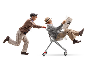 Senior pushing a shopping cart with another senior with a newspaper riding inside