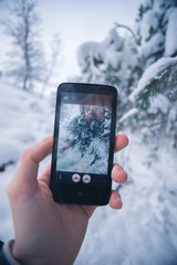 Traveler photographs a smartphone winter snowy forest.