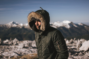 Man in outerwear on snowy mountains