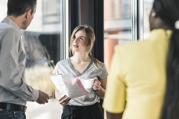Business people talking at the window in office