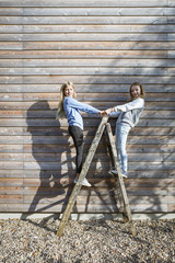 Two girls standing on a ladder in front of a wooden facade