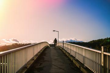 Woman riding a bicycle climbs the bridge