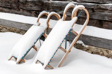 Eingeschneite Schlitten an einer Hüttenwand, Winterzeit