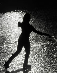 A woman skates in the sun over wet ice following heavy rain showers at the Tower of London ice rink in London, Britain