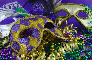Mardi Gras image of close up detail of carnival masks, beads, ribbons and confetti in purple, green, gold and black on purple background