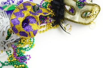 Mardi Gras border or frame of carnival masks, beads, ribbons and confetti in purple, green, gold and black on light background. Copy space