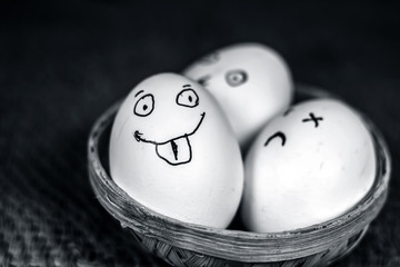 Funny faces drawn on the eggs which are in a traditional basket.