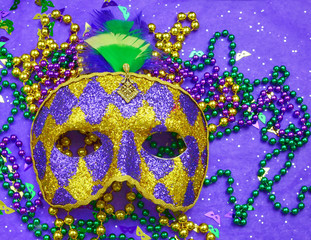 Mardi Gras image of harlequin mask, beads and confetti in purple, green, gold and black on background of rough textured sparkly paper