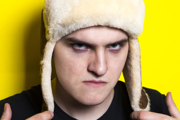 young athletic attractive man in a natural fur hat with earflaps and black t-shirt with a angry look on the contrast bright yellow background