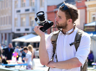 Man with beard holds photocamera on urban background