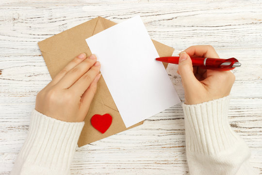 Hand of girl writing love letter on Valentine Day. Handmade postcard. Woman write on postcard for 14 February holiday celebration. Flat lay. Top view