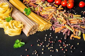 Various kind of italian raw Pasta. colorful fusilli pasta, spaghetti, fettuccine with tomatos on a black background. Closeup