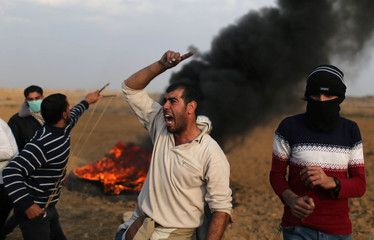 Palestinian demonstrator reacts during clashes with Israeli troops at a protest near the border with Israel in the southern Gaza Strip