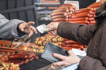 Customer buys meal at the street market in winter time. Vendor gets bill from customer as the payment for the meal. Customer still holds money in one hand, another hand holds open wallet.