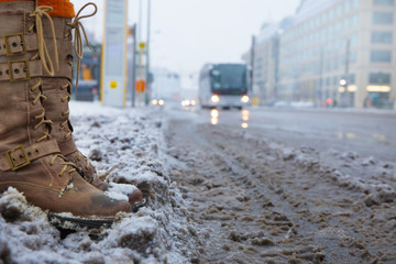 in a city, a woman is standing in the slush at a bus stop