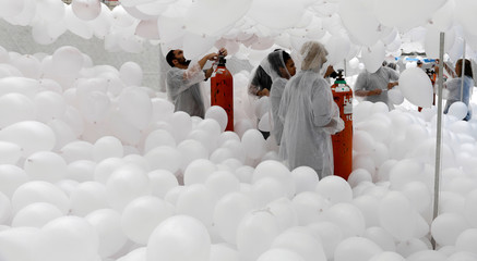 People prepare balloons to be released into the sky as a part of the year-end celebrations in downtown Sao Paulo