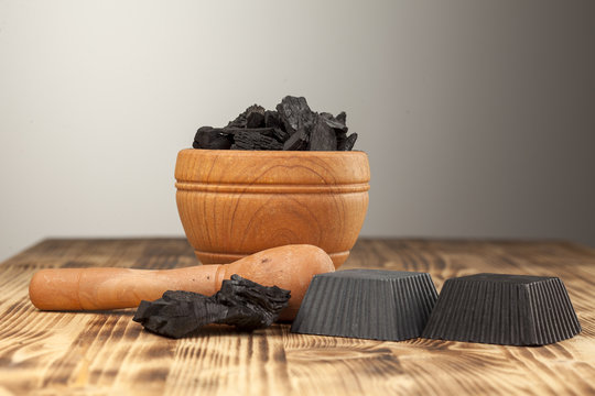 two hand maded black soap from activated carbon on a wooden plank