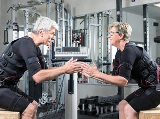 Pärchen im mittleren alter trainiert im Fitnessstudio mit einem EMS Gerät Stromimpulsgerät, Gummibänder, Kurzhanteln
