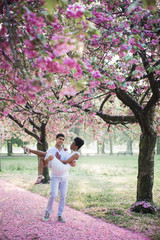 The young happy romantic couple walking by road with petals in the park and man holding woman in arms