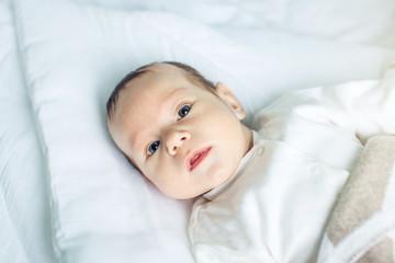 Cute funny baby lying on a white bed covered with a blanket. Concept of The tenderness of motherhood and family values
