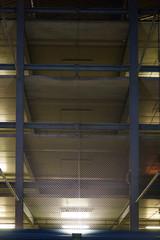 Beleuchtetes Parkhaus in der Nacht / Ein offenes Parkhaus mit mehreren Parkdecks geschützt durch Gitterdraht wird in der Nacht beleuchtet.
