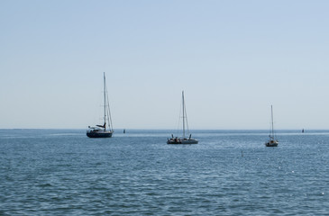 Hot midday on the Black Sea. Three sailing boats on the surface of calm sea.