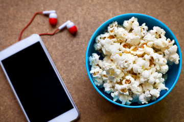 Smartphone and popcorn in bowl