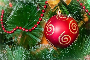 A beautiful red ball on a Christmas tree (or a New Year tree) with beautiful festive decoration ornament. New Year concept