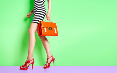 Wall Mural - Beautiful legs woman walking with red heels and orange bag. isolated on green wall.