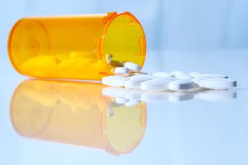White prescription pills spilling from medicine bottle on reflective surface