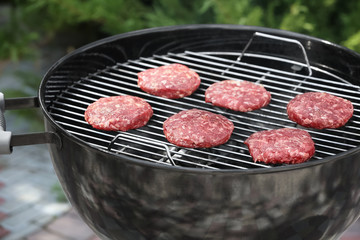 Barbecue grill with tasty patties on backyard