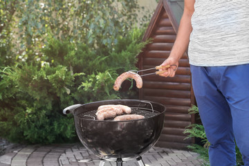 Man preparing delicious sausages on barbecue grill outdoors
