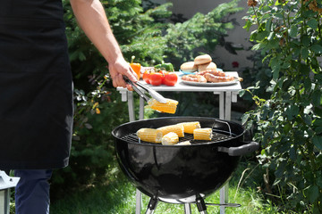 Man preparing delicious corn on barbecue grill outdoors