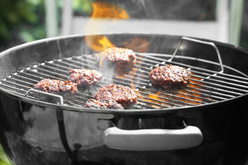 Delicious patties on barbecue grill outdoors