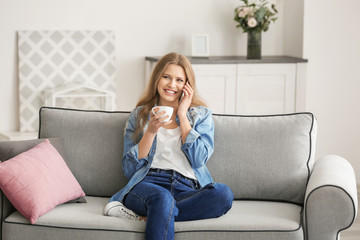 Beautiful woman speaking by cellphone while resting on sofa at home