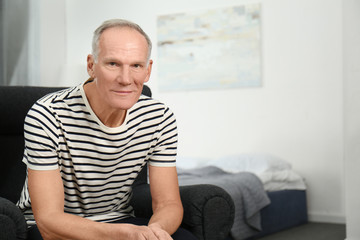 Attractive mature man in casual clothes indoors