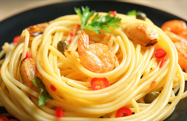 Delicious pasta with garlic and fried shrimps on plate, closeup