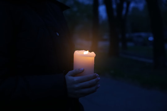 Woman holding burning candle outdoors late in evening