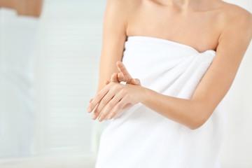 Young woman applying body cream in bathroom, closeup