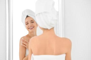 Young woman applying body cream in bathroom