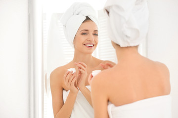Young woman with body cream in bathroom