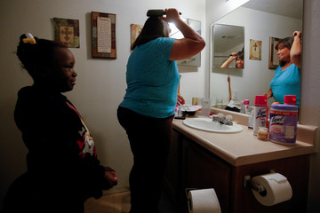 Warner, 6, watches as her neighbor Young brushes her hair in Houston