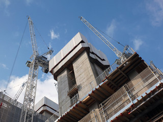 cranes working on a large modern construction site with concrete structures and blue sky