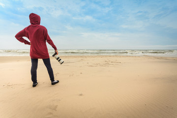 Woman walking on beach with camera