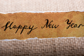 Happy new year written on a torn paper