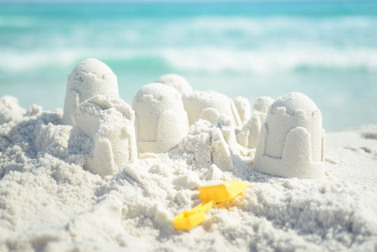 Sandcastle and shovel on Florida beach with white sand