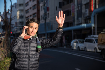 Man With Cellphone Hailing Taxi